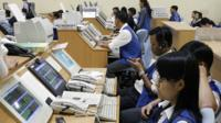Traders watch a stock index monitors at a Securities Trading Center in Ho Chi Minh City