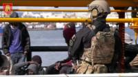 A Maltese soldier stands by migrants onboard Elhiblu 1