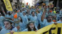 Amensty International human rights activists, dressed as the Statue of Liberty, wave banners while marching in protests against the NATO meeting in front of North Railway Station in Brussels, Belgium, 24 May 2017