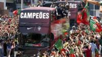Thousands of supporters cheer the players of the Portuguese national soccer team on an open-top bus along the streets of Lisbon