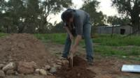 Mustafa Dawa digging a grave