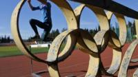 Athlete jumping over hurdle behind Olympic ring symbol