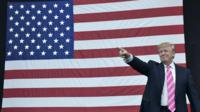 Donald Trump in front of a flag