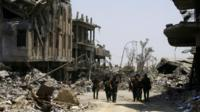Iraqi security forces walk between destroyed buildings in the Old City of Mosul, Iraq (10 July 2017)