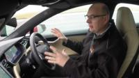 A man sits in a driverless car