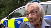 Anne outside a police car