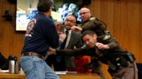 Randall Margraves (L) lunges at Larry Nassar (wearing orange) a former team USA Gymnastics doctor who pleaded guilty to sex abuse in November 2017