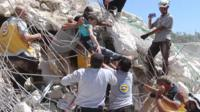 A child is pulled from a destroyed building after an explosion in Idlib, Syria