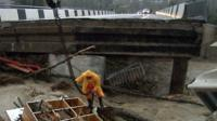 A road bridge destroyed by a river bursting its banks