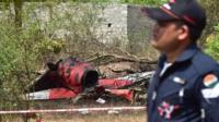An Indian Air Force personnel walks past the wreckage of an aircraft