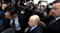 Banned Fifa president Sepp Blatter faces a media scrum in Zurich