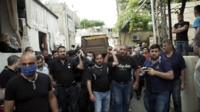 Mourners carrying Aya Hashem's coffin through the streets of her hometown of Koleileh, Lebanon
