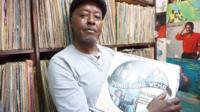 Stallholder holds vinyl record