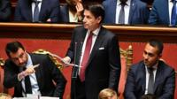 Italy's PM Giuseppe Conte addresses Senate flanked by Matteo Salvini (L) and Luigi Di Maio (R)