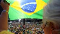 Protester holds up a Brazil flag