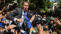 Venezuelan opposition leader Juan Guaido shouts surrounded by journalists on his way to the National Assembly