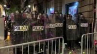 Riot police stand in formation after being pelted with paint