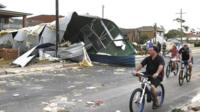 "Residents from Sydney""s southern suburb of Kurnell cycle past the damaged homes"