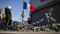 People stand in front of a makeshift memorial in front of Le Petit Cambodge restaurant in Paris, scene of one of the deadly attacks on 13 November