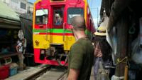 People watch a train move through Maeklong Station market