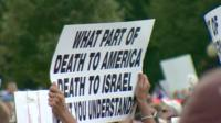 A protester holding a sign reading 'What part of death to America, death to Israel don't you understand?'