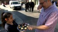 Girl handing out cakes