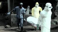 Gravediggers carrying body