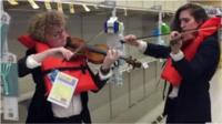Two women play violins in a supermarket wearing lifejackets