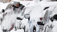 Man clears snow off car in Moscow