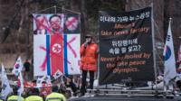 Protesters hold a sign with North Korean leaders' faces crossed out.