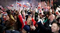 People waving Union Jack flags