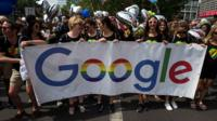 People march with a Google banner