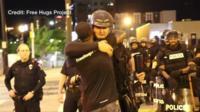 Ken Nwadike hugs a police officer