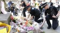 Flowers being laid by police officers in St Ann's Square, Manchester