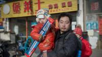 A man holds his son outside a toy store in China