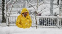 A man walks during snowfall in Yantai in China's eastern Shandong province on 12 December 2017