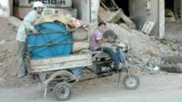 Boy driving rickshaw laden with posessions
