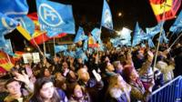 Mariano Rajoy's supporters wave flags