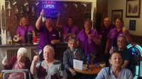 Residents and staff raise their glasses at the care home bar