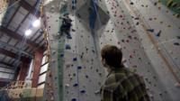 Matthew on the rock climbing wall as his friend Max watches