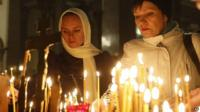 People light candles inside a church in St Petersburg, Russia