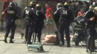 Riot police with injured man on ground