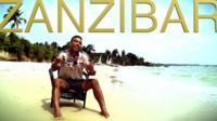 Ikenna Azuike sitting on a chair on a beach