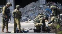 Israeli soldiers tend to their injured colleague next to the corpse of a dead Palestinian