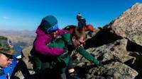 Группа в 27 человек помогала туристке взбираться на вершину.