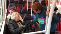 Chatty bus volunteer talking to passengers