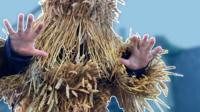 Man in straw bear outfit