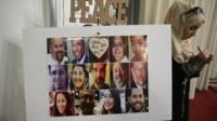 A Muslim woman writes a message near a photo of the 14 victims in the San Bernardino attacks