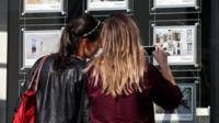 Women look at estate agent window