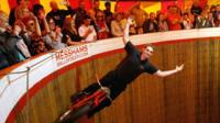 A performer riding the wall of death